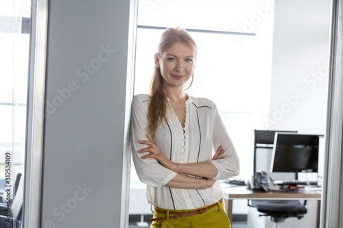 Portrait of smiling young businesswoman with arms crossed in doorway of office Canvas Print