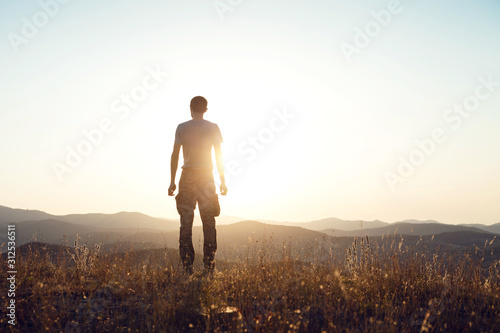 Fototapeta The guy climbed the top and looks at the mountains. Dawn in nature, the beginning of a new day obraz