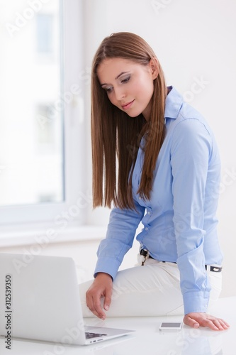 Vászonkép Beautiful businesswoman sitting on desk and looking at laptop