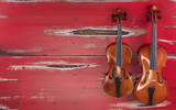 two violins on a red wooden background
