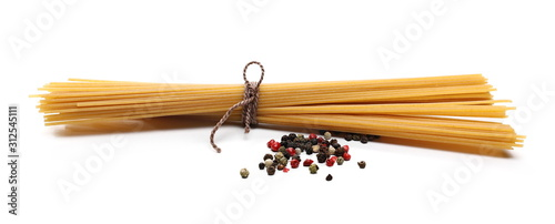 Fotografia Raw spaghetti bundle tied with string and mixed, colorful peppercorns isolated o
