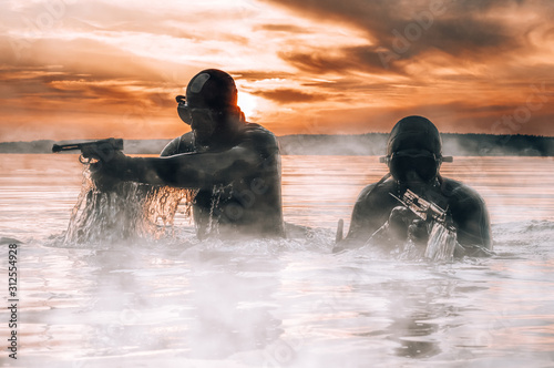 Obraz Team of fighters of a special unit move on water to complete the task. The concept of instability, military operations, the cold war. - fototapety do salonu