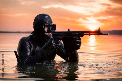 Obraz The marine comes out of the water and moves toward the target with weapons in hand. The concept of video games, advertising, instability in the world, country conflicts. - fototapety do salonu