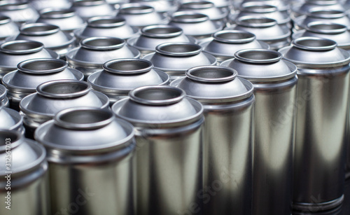 Photo A large number of aerosol cans on a black background.