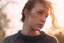 Portrait Of A Beautiful Girl With Red Fiery Curly Hair In A Sweater Over A Sky Background In The Warm Sunshine