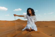 Woman Standing Sitting In Sandy Dunes In Desert