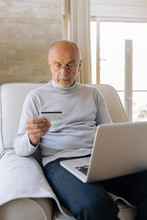 Portrait Of A Senior Man Using Laptop At Home