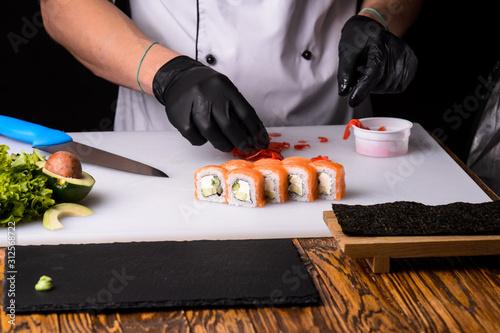 Fototapeta Chef cooks maki in stages obraz