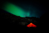 Burning red tent in night with polar lights