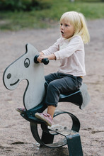 Little Child Riding On The Swing Horse