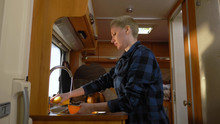 A Woman Washes Dishes In A Motorhome. Car Travel Concept