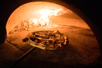 A traditionally made pizza going into a wood fire oven