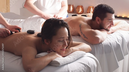 Beautiful pleasant couple having good time in modern wellness salon, lying on ma Fototapeta