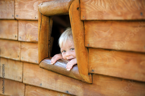 Fotografia, Obraz Curious child, toddler boy, peering from a small window in wooden shrub