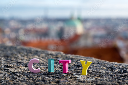 Fototapeta word City of colored letters on the background of the city obraz