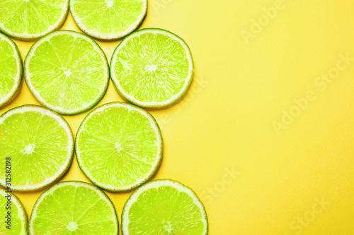 Fototapeta Limonka  soczyste-plastry-swiezej-limonki-na-zoltym-tle-lezal-plasko-miejsce-na-tekst