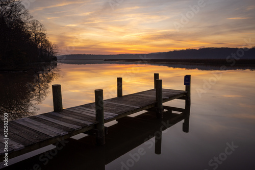 Fototapeta Dock at Sunrise on a Calm Morning with Orange Sky and Reflections obraz