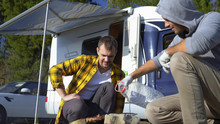 Two Men Cook Meat On The Grill Near The Campervans In Nature