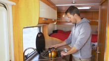 A Man Washes Dishes In A Motorhome. Car Travel Concept