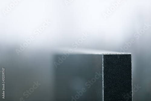 Photo Black granite tombstone on blurred background, closeup with space for text
