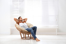 Attractive Man Relaxing In Papasan Chair Near Window At Home. Space For Text