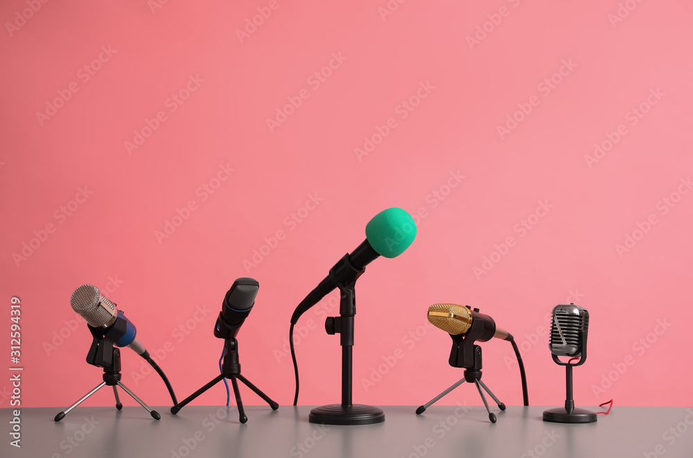 Fototapeta Microphones on table against pink background. Journalist's work
