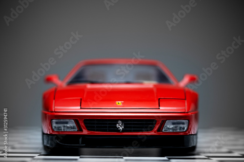 Photo Red toy Ferrari 348TB sports car close up product shot on a chequered ground and gray background