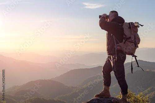 Foto  Young man with backpack enjoying sunset on binoculars peak of mountain layers line