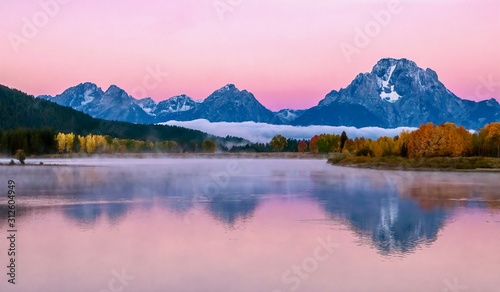 Cuadros en Lienzo The beautiful pink alpenglow over the dramatic Teton mountain range at sunrise on an autumn morning