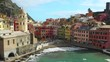 Vernazza, Cinque Terre, Liguria, Italy - Waves Splashing To The Shore With Colorful Houses, Tourists Enjoying The Beautiful Scenery On A Sunny Day - Aerial Drone Shot