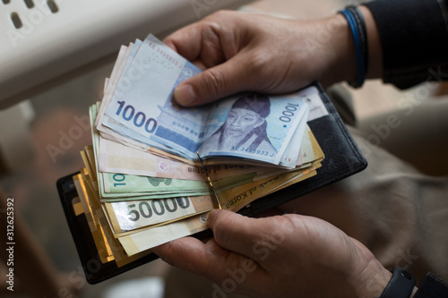 Fototapeta Hand holding South korean Won banknotes isolated obraz