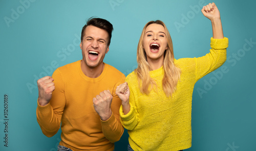 Obraz Joyful mood. Excited couple is posing on emerald background, wearing yellow sweaters and expressing happiness and victory with their poses, gestures and facial expressions. - fototapety do salonu
