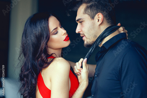 Tempting milf woman in red holding young lover by tie Wallpaper Mural