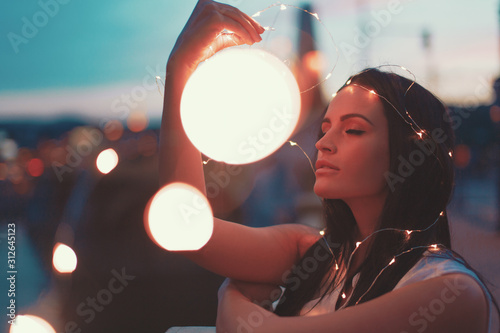 obraz dibond Young brunette woman playing with fairy lights outdoors moody moments