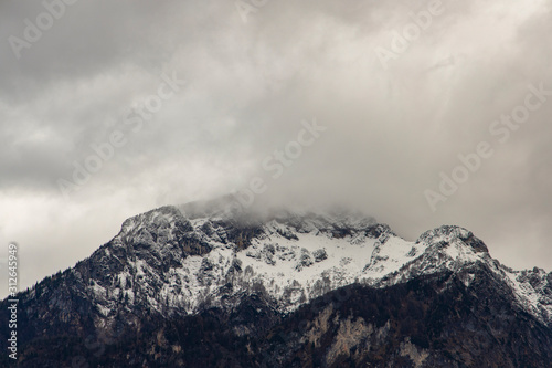 gorgeous dramatic mountain snowy peak winter time foggy cloudy sky picturesque landscape nature wallpaper background concept picture with empty copy space for your text or inscription