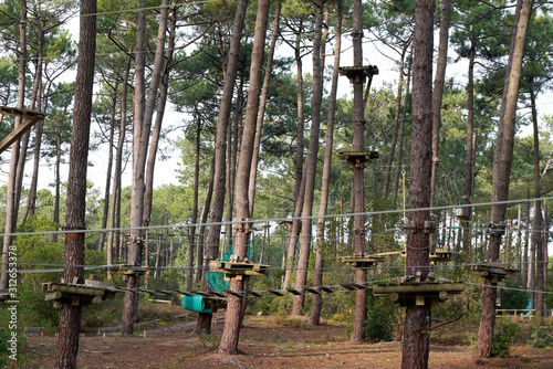 Fotografía ropes course in treetop adventure park passing hanging rope obstacle