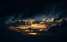 Dramatic Dark Evening Sky Landscape With Moody Clouds And Golden Sunlight