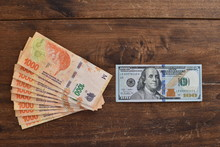 100 Dollar Bill With Argentine Peso Bills, Symbolic For Money Exchange Rate