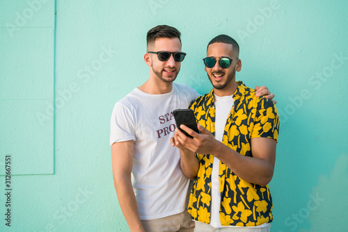 Gay couple spending time together while using phone. Wallpaper Mural