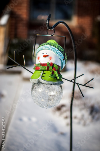 A little iceman ornament in a yard covered in snow Tableau sur Toile