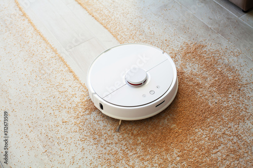 Fototapeta Smart House. Vacuum cleaner robot runs on wood floor in a living room obraz na płótnie