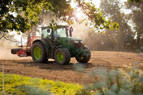 Carta da parati Tracteur au champ en train de labourer la terre.