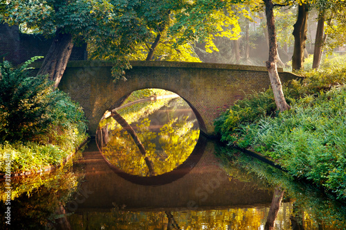 Stone old bridge reflection in the form of a circle in water of a canal in a park, Den Bosch, The Netherlands