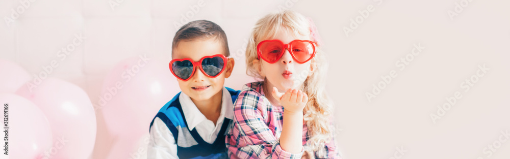 Fototapeta Valentine day holiday celebration. Web header banner for website. Two happy Caucasian cute funny children kids wearing heart shape glasses. Boy and girl hugging. Love, friendship and fun.