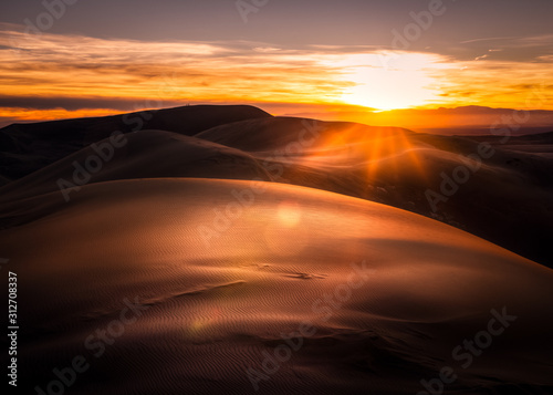Sun setting over sand dunes in Colorado. The sky and sand is very orange. There are sun rays and a little lens flare.