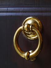 Polished Brass Door Knocker On A Dark Wood Door
