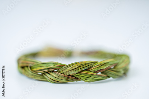 Valokuva Close up of middle of green fresh sweetgrass braid tied in a circle isolated on