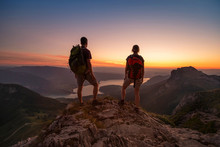 Travel To Alps Mountains, Tourists Hikers With Backpacks At Sunset Enjoying Panoramic View