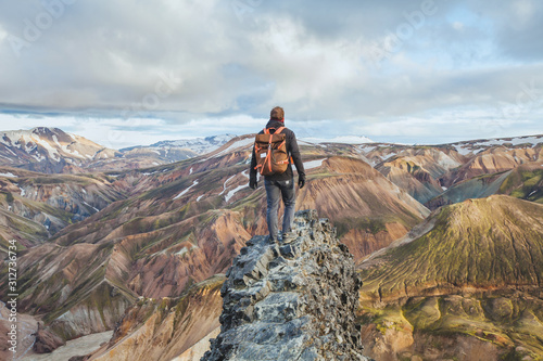 Fototapeta adventure travel, hiking in Iceland with backpack, tourist looking at colorful landscape of Landmannalaugar obraz