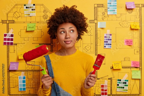 Obraz Contempative curly female interior designer with paint roller and brush, does repairing in room, thinks how to improve design project of new apartment. Repair, designing and flat renewal concept - fototapety do salonu